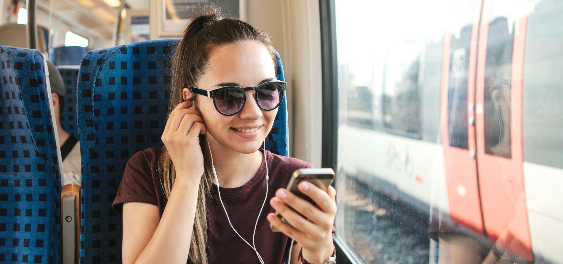 Junassa istuva nainen katsoo kännykkää kuulokkeet korvilla